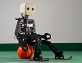 A robot sits on a soccer ball