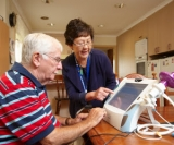 Telehealth nurse shows patient how to use home monitoring system